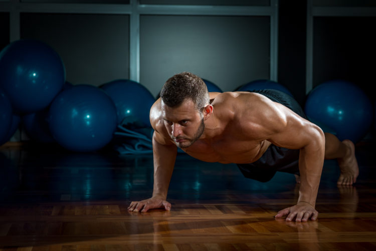 Image of Young adult man doing push-ups in gym.