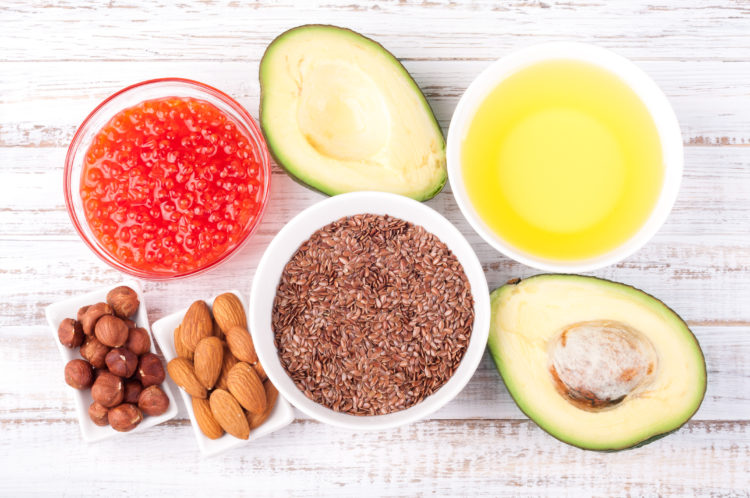 Image of Healthy fats. Sources of omega 3 - avocado, olive oil, red caviar, nuts and flax seed on wooden background. Healthy food concept. Top view
