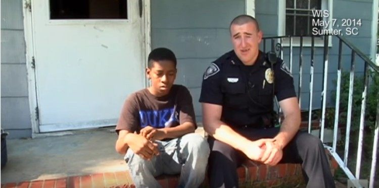 Officer Acerra sits next to Cameron Simmons on porch