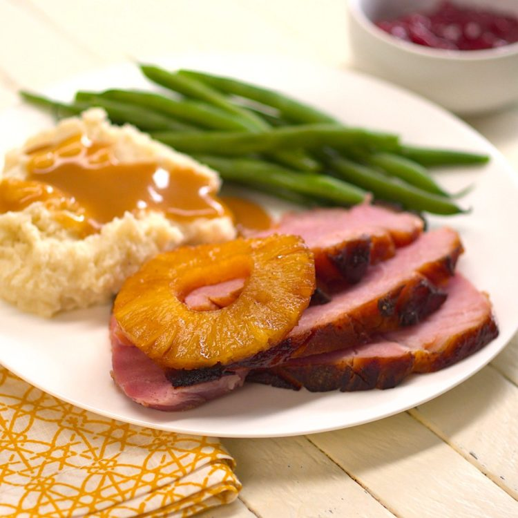 Old Fashioned Baked Ham with Pineapple & Maple Brown Sugar Glaze plated mashed potatoes gravy green beans