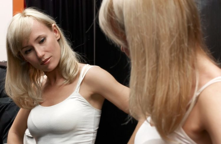 Woman looking at her breasts in mirror.