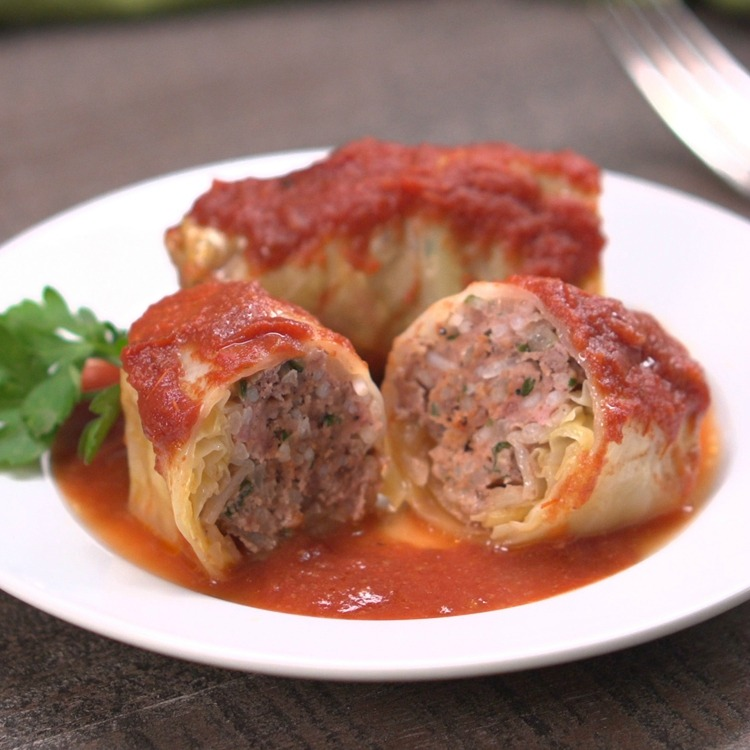 Cabbage rolls on white plate, 1 cut in half