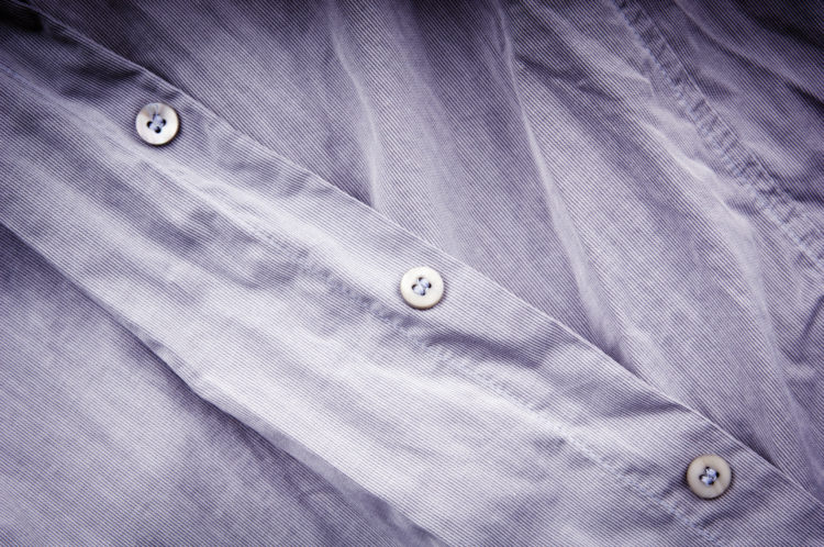Image of crumpled, creased un-ironed business shirt and buttons