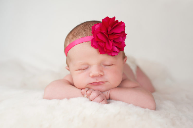 Image of A portrait of a beautiful newborn baby girl wearing a hot pink flower headband. She is sleeping on a cream colored sheepskin rug.
