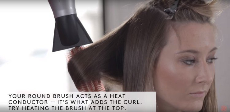 Using round brush to curl the ends of hair.