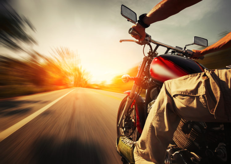 Image of Biker riding motorcycle on an empty road at sunny day