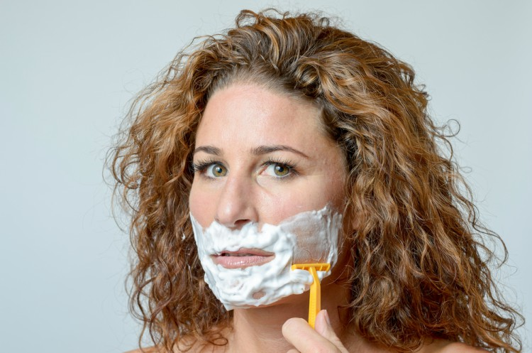 Image of middle aged woman shaving her face.