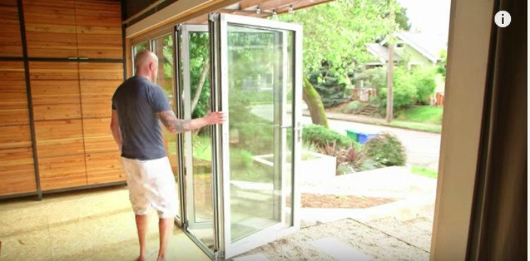 man opening accordion glass door