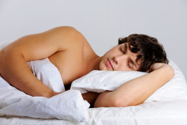 man sleeps in white sheets