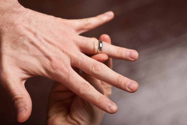 Ring being placed onto man\'s finger stuck
