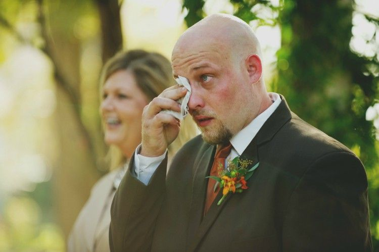 Groom wiping tears from face.