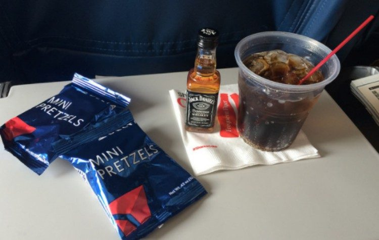 mixed drink and pretzels on plane