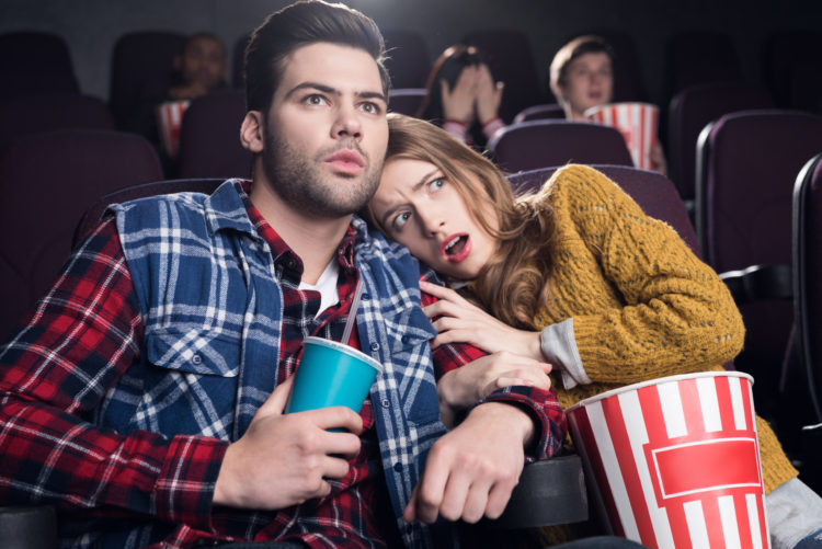 Image of couple watching horror movie in theater