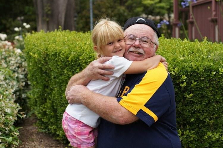 Image of grandfather hugging child.