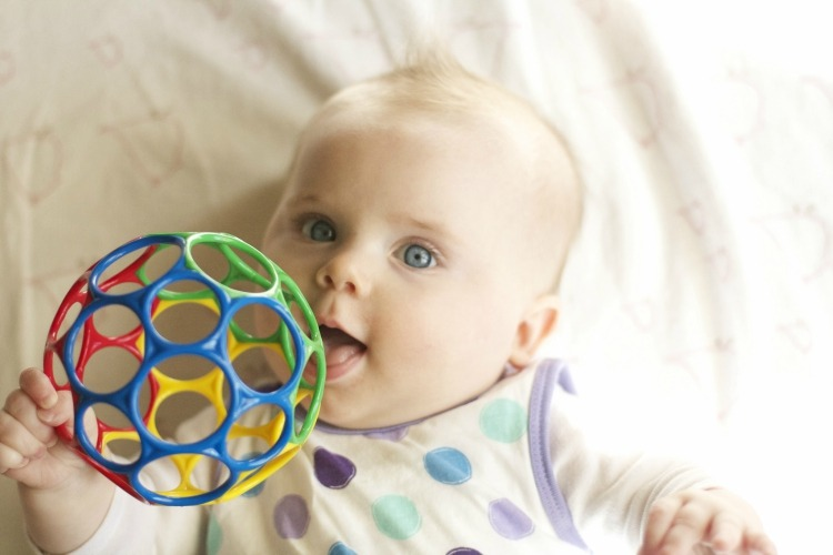 Baby with red, blue, yellow and green ball toy