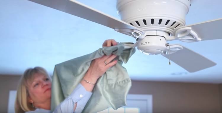 woman placing pillowcase on ceiling fan