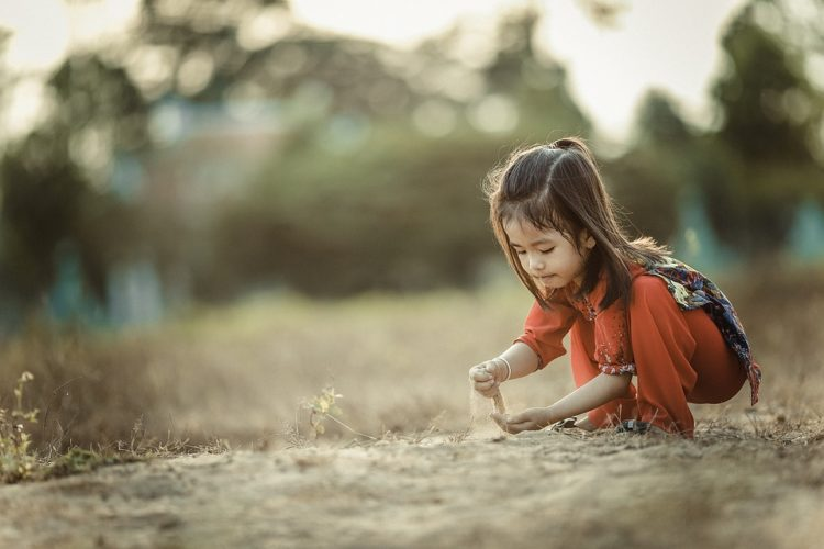Image of girl playing in grass by herself