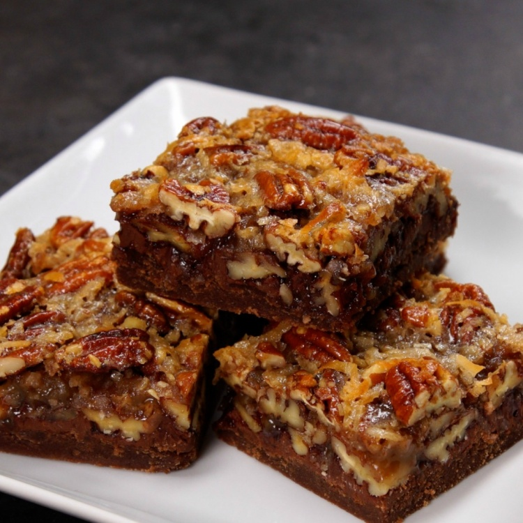 4 German chocolate pecan bars on a white plate