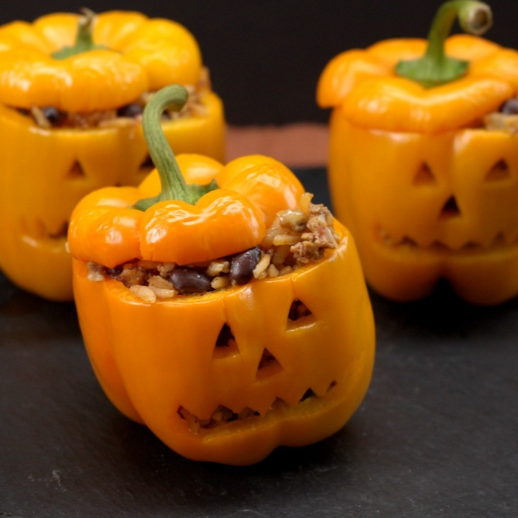 Stuffed orange peppers cut to look like jack-o'-lanterns