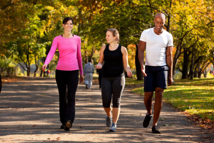 Image of three people walking in a park, getting some exercise