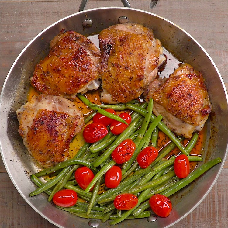 Juicy chicken thighs coated in mouthwatering honey garlic glaze and baked till crispy with green beans and & tomatoes (so you don't have to make a side dish!)
