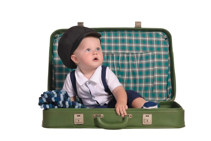 baby boy traveller wearing a hat sitting in green checkered old-fashioned suitcase