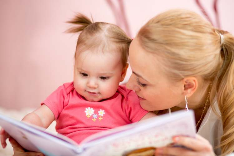 Image of mother and baby girl reading book.