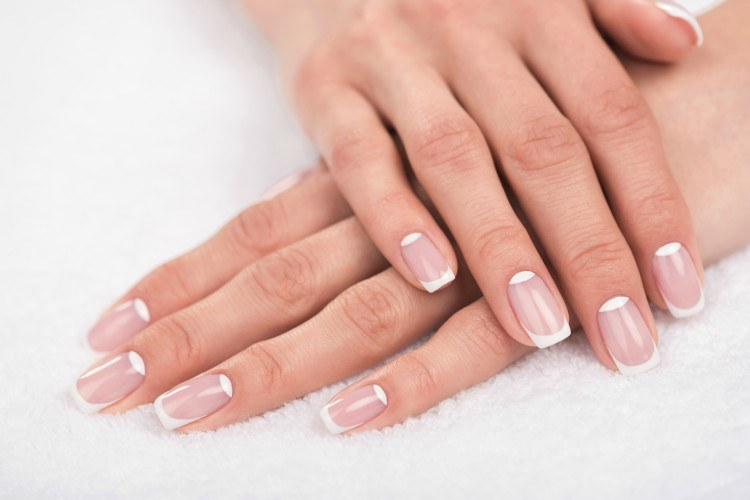 Image of hands displaying a French manicure.