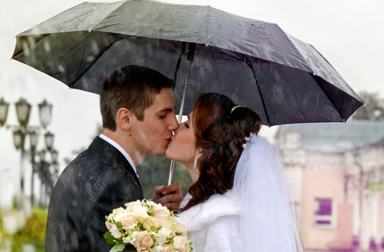 Pic of couple kissing in rain at wedding.