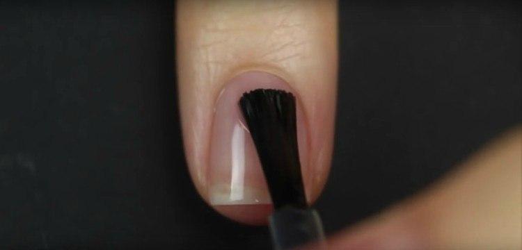 Woman applying nail base coat.