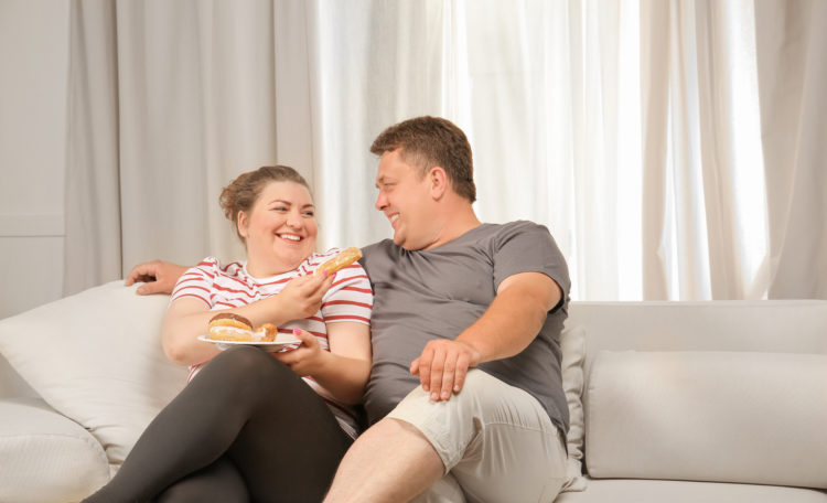 Image of Overweight couple eating sweets on sofa at home