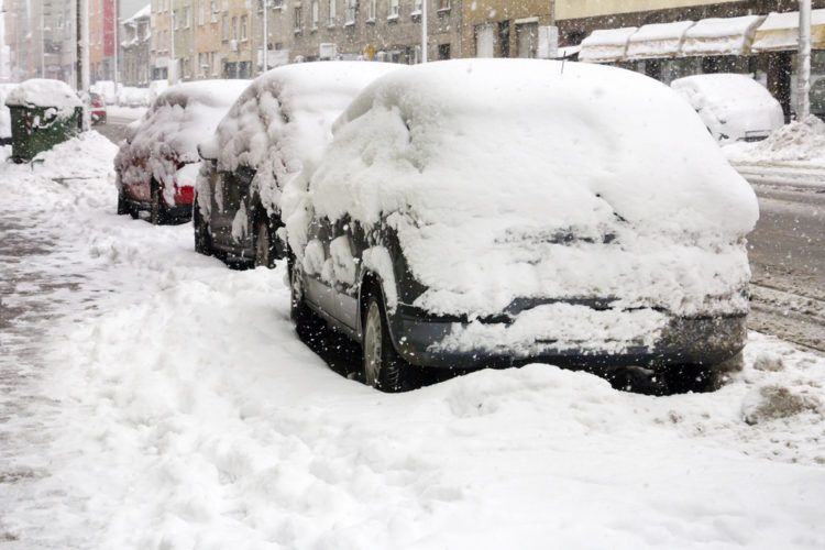Cars covered with fresh snow on the street.