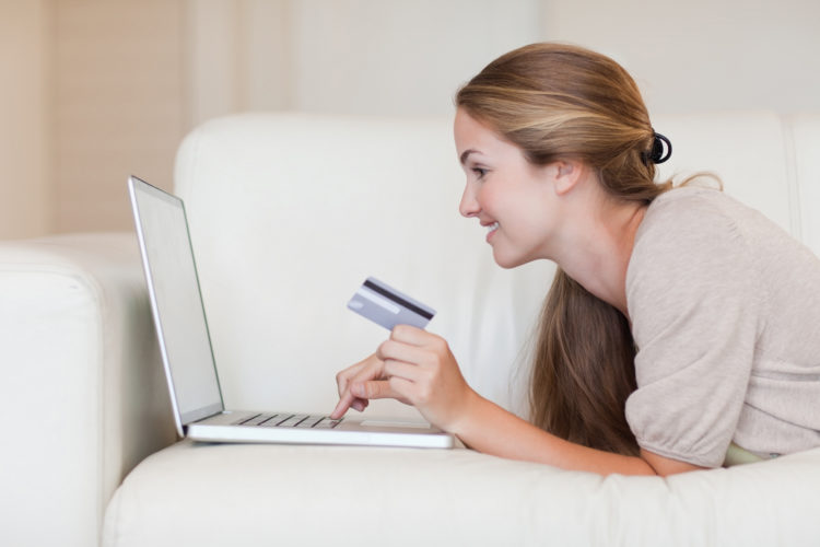 Side view of woman on the sofa shopping online