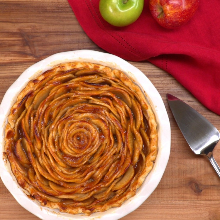 Overhead pic of apple rose pie on wood table with server