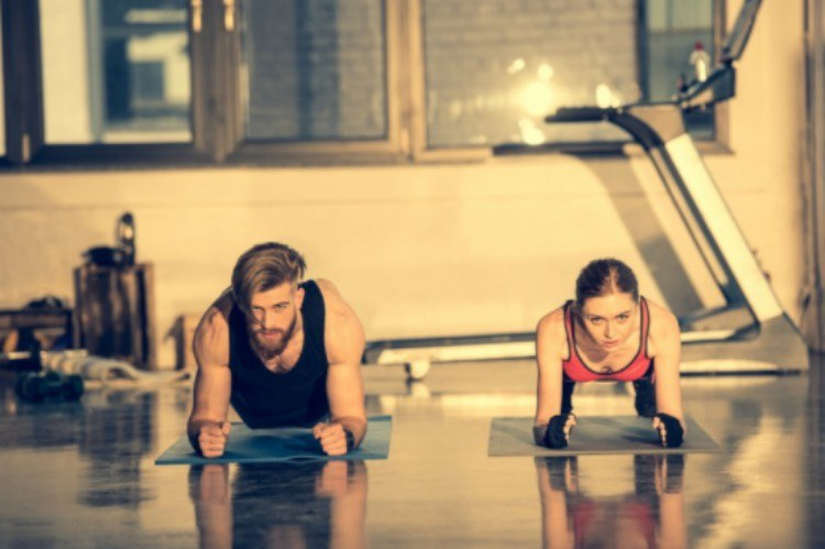 man and a woman plank in a gym