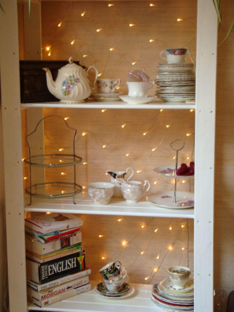 Shelves backed with fairy lights.