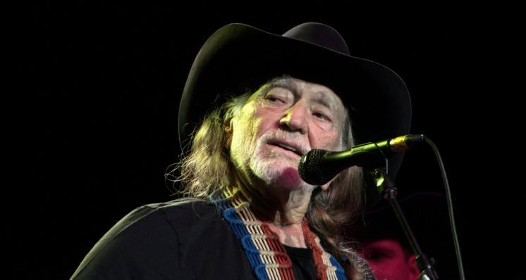 Willie Nelson performing on stage