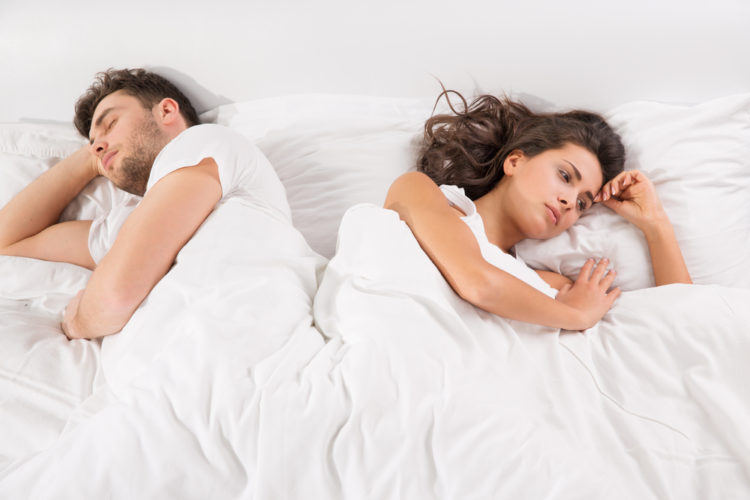 Image of upset young couple having disagreement lying side by side in bed facing in opposite directions