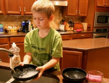 Image of young boy washing dishes