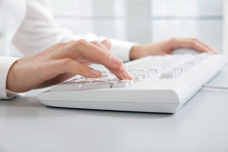 Image of hands touching computer keys during work
