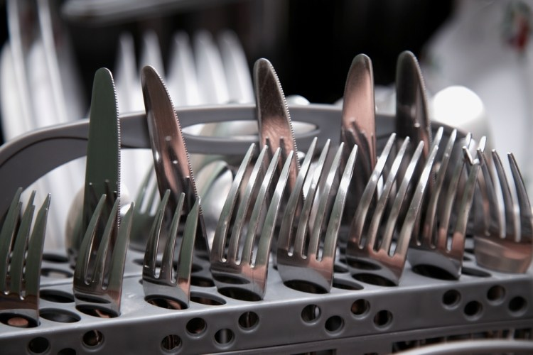 Knives and forks loaded prongs and sharp point up in dishwasher