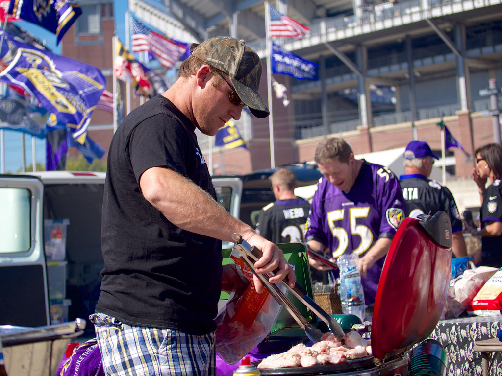 Man grilling at tailgate party.