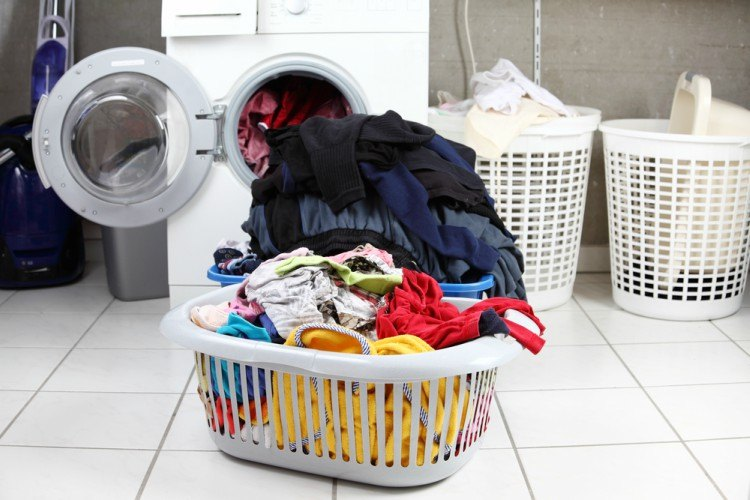 overflowing laundry baskets near washer and dryer
