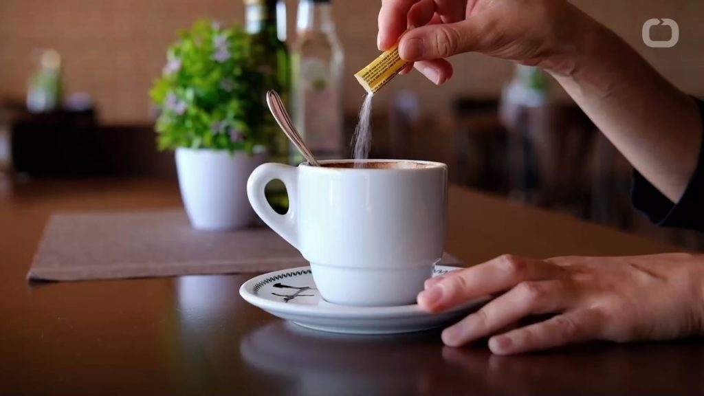 packet of sugar being poured into coffee