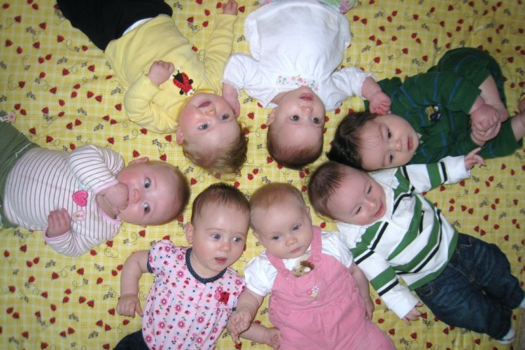 7 babies lying in a circle