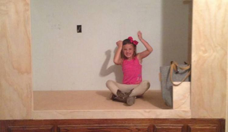 kid sits in unfinished cabinet bed