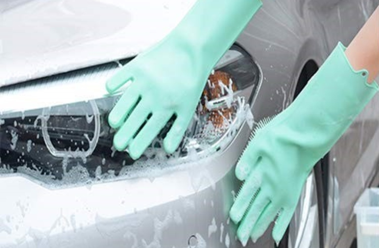 Car being washed with silicone bristle gloves.