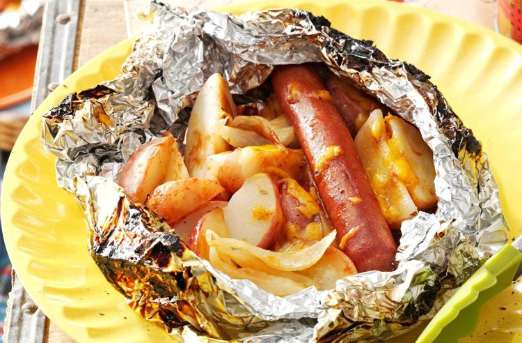 Cheesy hot dogs and potatoes in foil.
