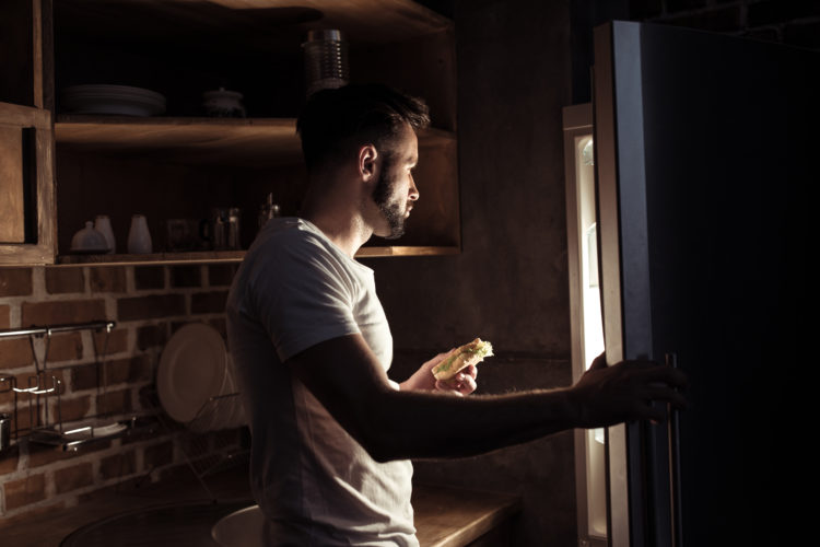Image of man looking into refrigerator at night