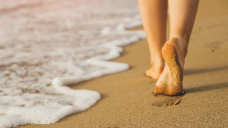 Image of feet walking on sand at the beach